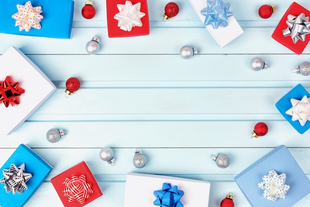 Gift boxes with bows and christmas balls are lined up in a circle on blue