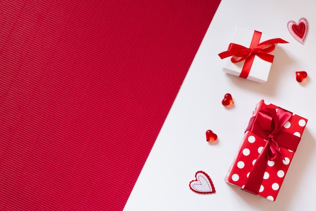 Gift boxes with bows and hearts on red and white background.