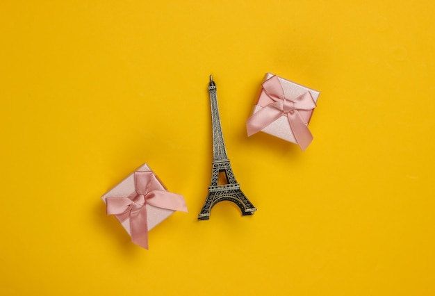 Gift boxes with bows and statuette of the eiffel tower on yellow background. shopping in paris, souvenirs