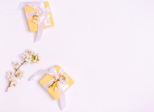 白い背景の上の開花桜の枝とギフトボックス。フラットレイ、はがき用の空白、3月8日、母の日、バナー、コピースペース。上から見る
