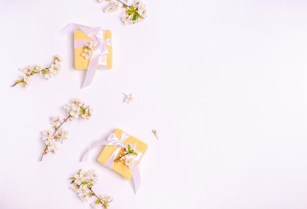 복사 공간 흰색 바탕에 꽃이 만발한 벚꽃의 가지와 선물 상자. 평면 배치, 3 월 8 일, 어머니의 날, 배너, 텍스트를위한 장소. 위에서보기
