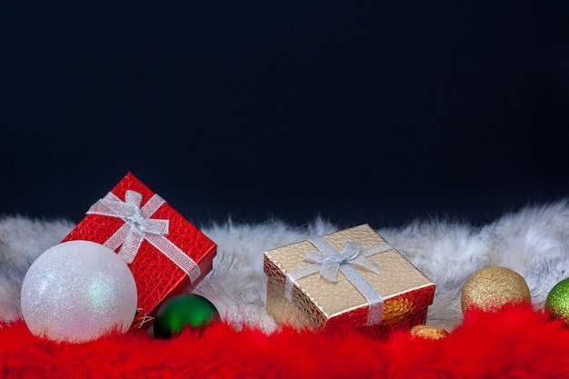 Gift boxes with christmas balls on white and red fur. red and gold boxes. christmas card. copy space on top on a dark background.