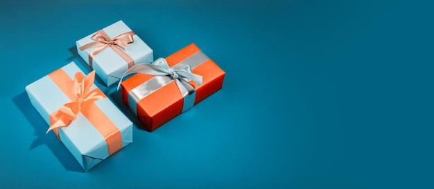 Подарочные коробки с разными цветами на шаблоне баннера. синяя подарочная коробка и желтый бант на смелом синем фоне. Premium Фотографии
