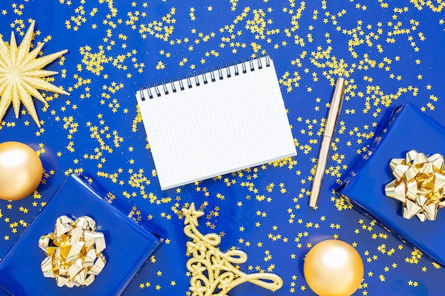 Gift boxes with a golden bow and fir tree with christmas balls on a blue background, golden shiny glitter stars , open spiral notepad and pen, flat lay, top view
