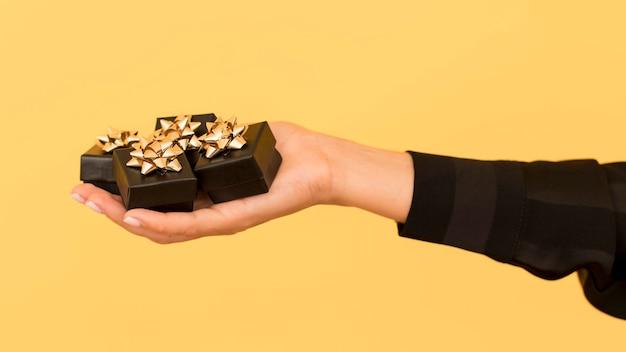 手に持ったブラックフライデーのゴールデンリボン付きギフトボックス