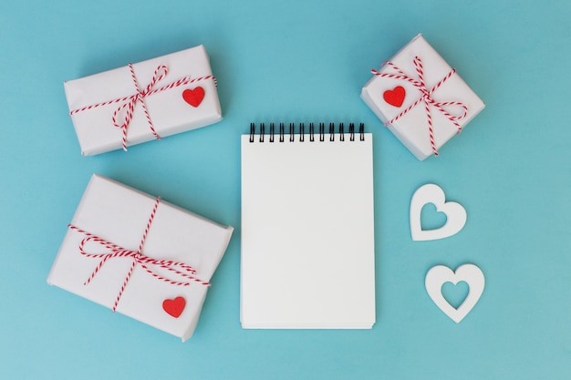 Gift boxes with notepad and hearts on table
