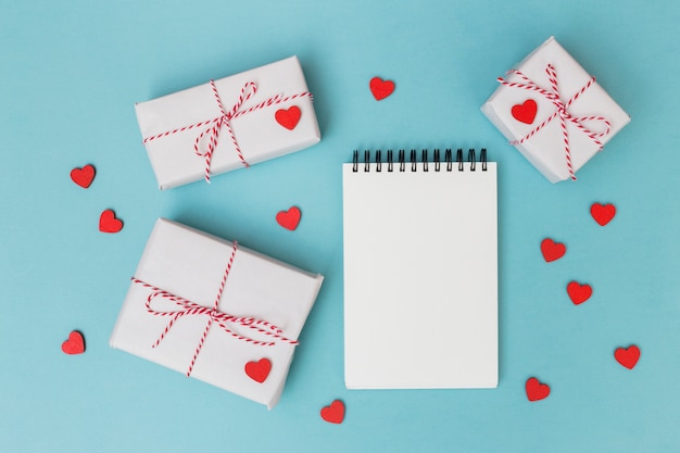 Gift boxes with notepad and red hearts on table
