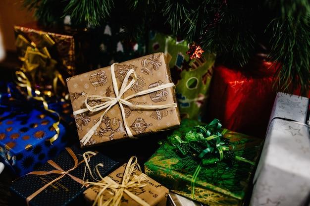 クリスマスツリーの近くに飾りが付いたギフトボックス。テキストの場所。スタイリッシュなラップギフト。メリークリスマスと新年あけましておめでとうございますのコンセプト。テキスト用のスペース。幸せな休日。側面図。