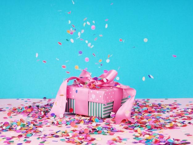 Подарочные коробки с бумажным конфетти. подарочная коробка на розовом столе вокруг праздничного конфетти.