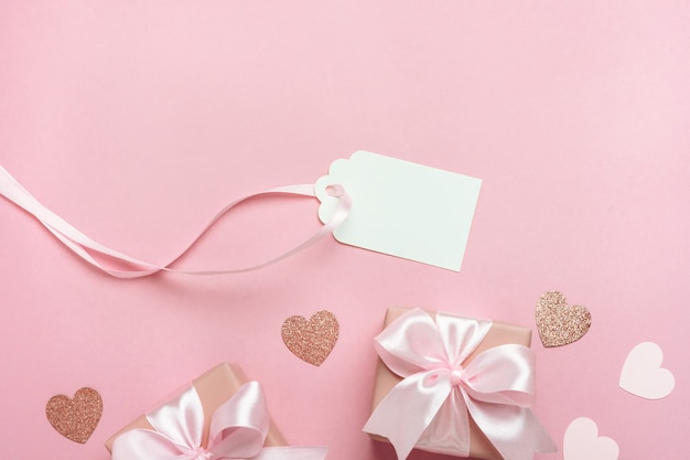 Gift boxes with pink ribbon and hearts on pastel pink background.