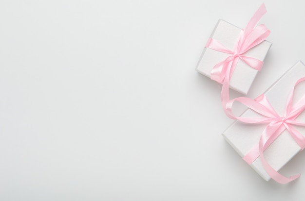 Gift boxes with pink ribbon on white background.