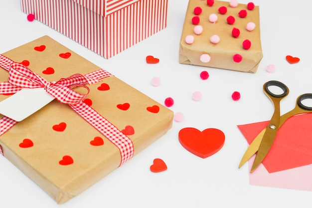 Gift boxes with red heart on light table