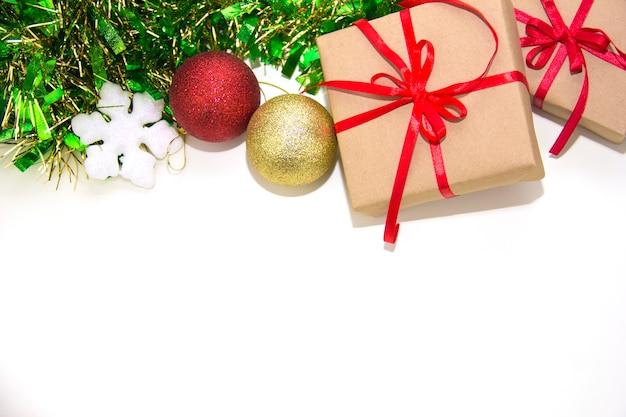 빨간 리본과 크리스마스 장식이 있는 선물 상자는 흰색 배경에 배치됩니다. 나무 배경에 매달려 패브릭 크리스마스 장식