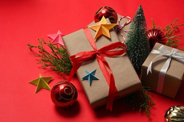 赤いリボンと赤い背景にクリスマスの飾りの装飾が施されたギフトボックス。