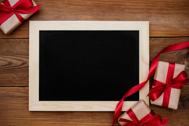 赤いリボンと木製のテーブルに空の黒板のギフトボックス。上面図。