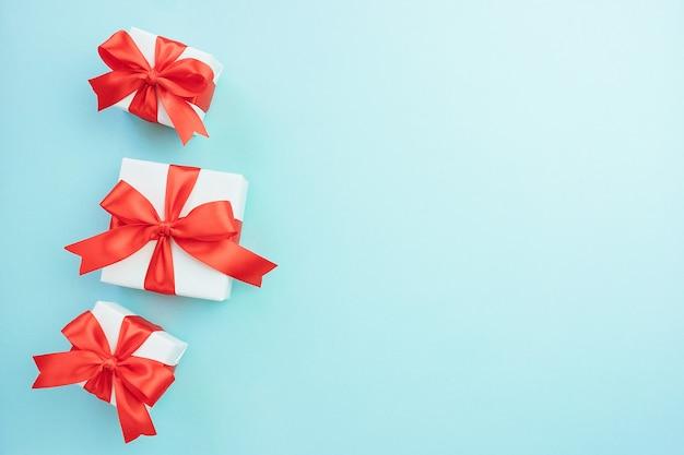 Подарочные коробки с бантом из красной ленты, изолированные на синем фоне. подарок на рождество, день рождения или день святого валентина. праздничный фон декора. вид сверху плоская планировка со свободным пространством.