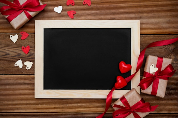 Gift boxes with red ribbon and empty chalkboard on wooden table. top view.