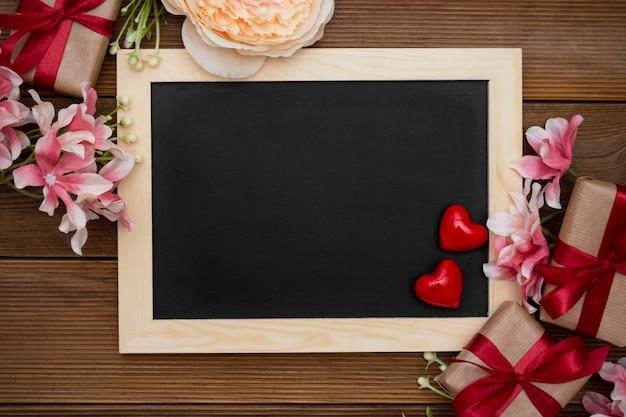Подарочные коробки с красной лентой, цветочной композицией и пустой доской на деревянном столе.