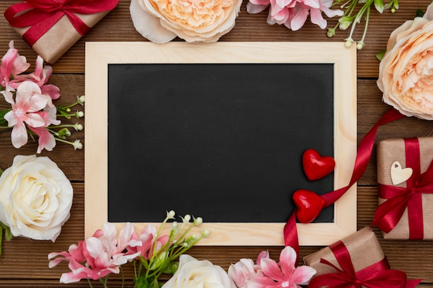 Gift boxes with red ribbon, flower arrangement and empty chalkboard on wooden table.