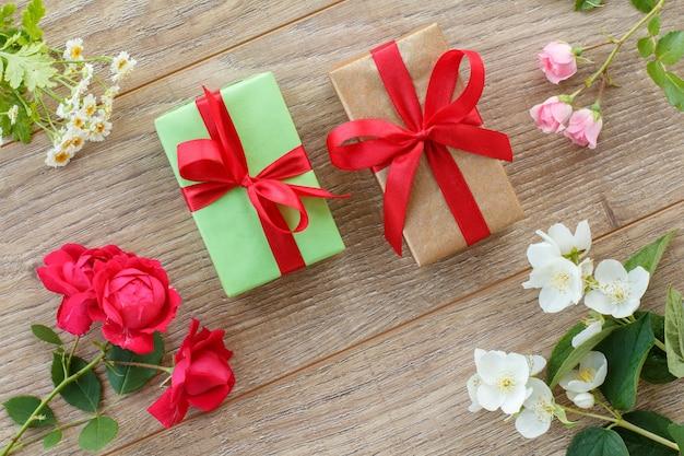 赤いリボンと美しいバラ、ジャスミンとカモミールの花が木製の背景にギフトボックス。休日に贈り物をするという概念。上面図。