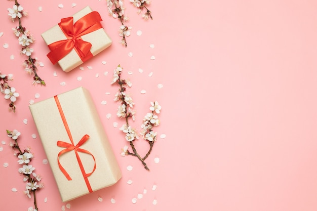 Gift boxes with red ribbons, flower branches