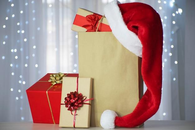크리스마스 조명 bokeh와 종이 봉지 위에 산타 모자와 선물 상자