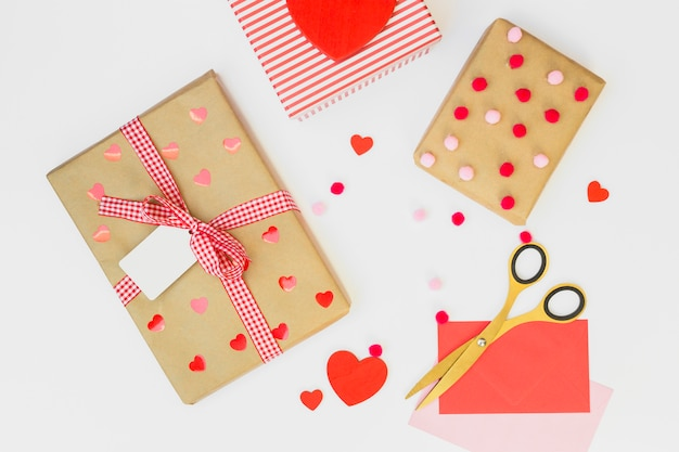 Gift boxes with small red hearts on table