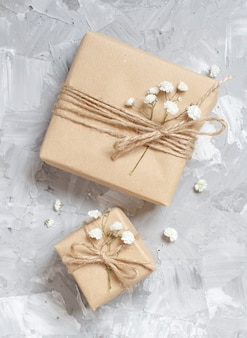 Gift boxes with small white flowers on a grey background
