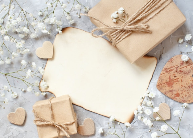 Gift boxes with small white flowers and hearts on a grey background