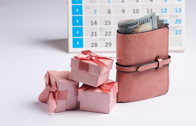 財布、白い背景の上のデスクトップカレンダーとギフトボックス。ホリデーショッピング、ブラックフライデー、毎月の特別オファーのコンセプト