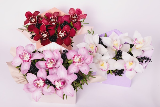 Gift boxes with white, burgundy and pink orchid cymbidium on white