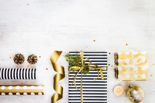 Gift boxes wrapped in black and white striped and golden dotted paper with, pine, cones, candle and wrapping materials on a white wood old background. christmas presents preparation. empty space.