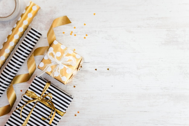 Gift boxes wrapped in black and white striped and golden dotted paper and wrapping materials