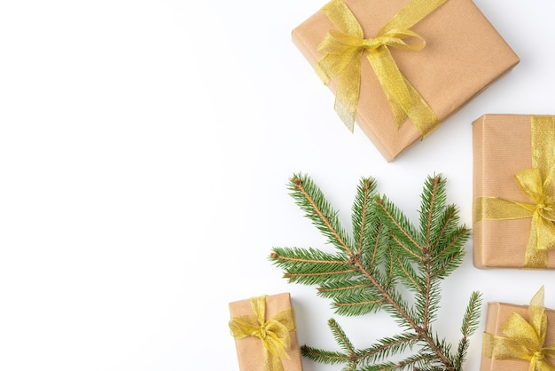 Gift boxes wrapped in brown paper and tied with a golden ribbon on a white background, top view, copy space