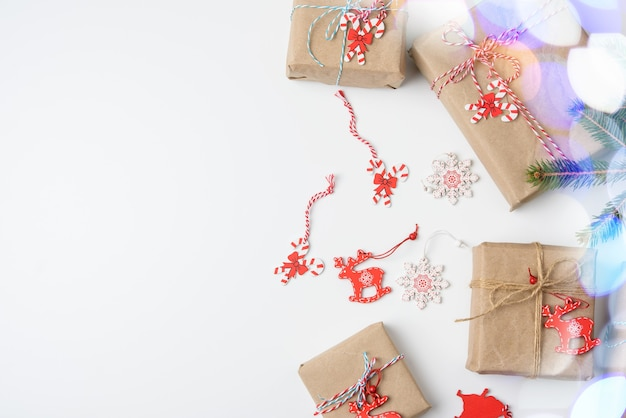 Gift boxes wrapped in brown paper and tied with a golden ribbon on white with bokeh, top view