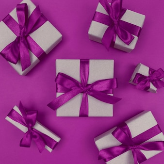 Gift boxes wrapped in a craft paper with purple ribbons and bows. festive monochrome flat lay.
