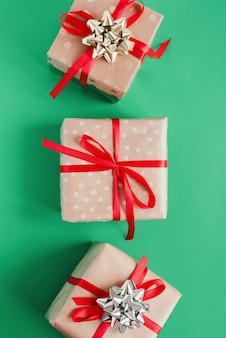 Gift boxes wrapped in craft paper with red ribbons and golden and silver bows on green background