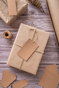 Gift boxes wrapped in craft paper with tags and labels on wooden  top view flat lay
