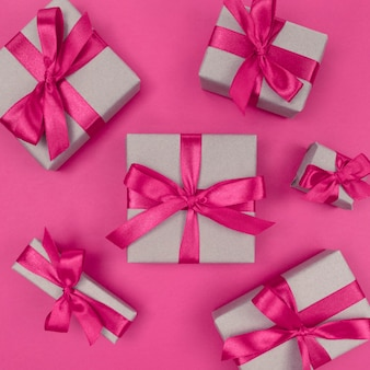 핑크 리본과 리본이 달린 공예 종이에 싸인 선물 상자. 축제 단색 평면 누워.