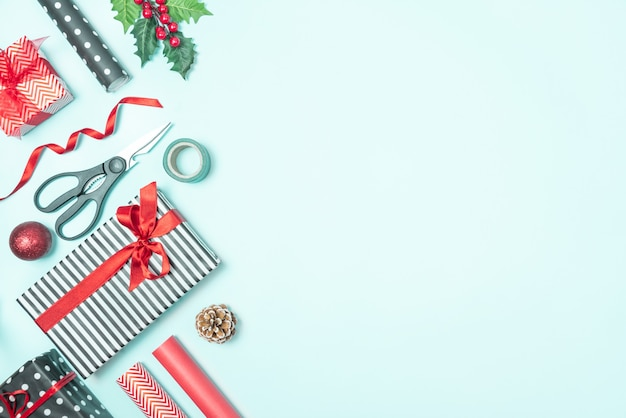 青の背景の上に包装材料で黒と白の縞模様と赤の紙で包まれたギフトボックス。クリスマスプレゼントの準備。