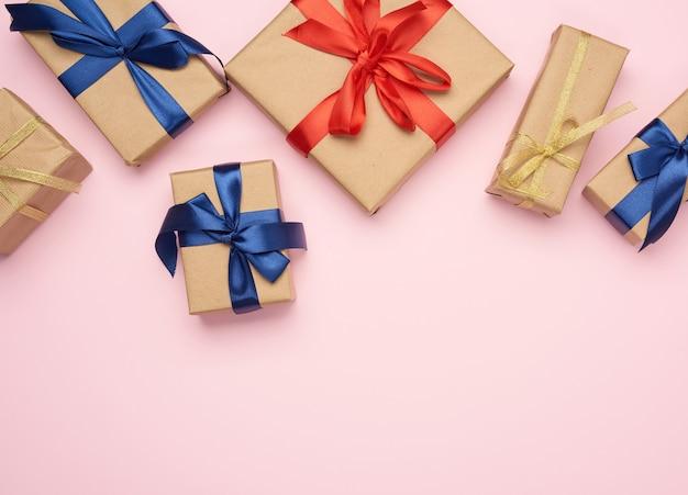 Подарочные коробки, завернутые в коричневую бумагу и перевязанные красно-синим бантом