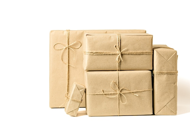 Gift boxes wrapped in recycled craft paper tied with twine on white background