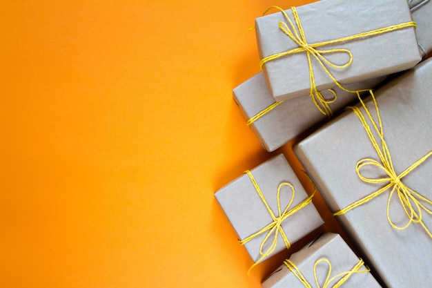 Gift boxes wrapped in recycled paper tied with yellow twine