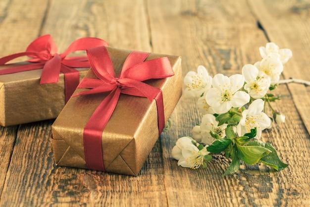 ジャスミンの花で飾られた木の板に赤いリボンで包まれたギフトボックス。色調が変わりました。