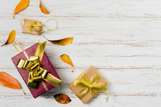 Gift boxes in wrapping paper with ribbons and autumn leaves on a white wooden background