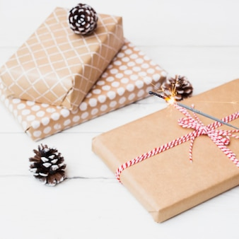 Gift boxes in wraps near snags and burning bengal light