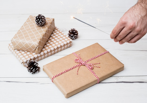 Gift boxes in wraps near snags and hand with burning bengal light