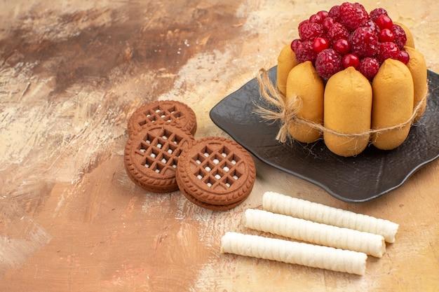 Una torta e biscotti del regalo sui frutti marroni dei piatti sulla vista superiore del tavolo di colore misto