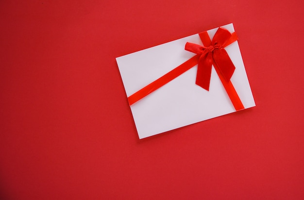 Gift card on red background with red ribbon bow gift voucher on red background top view copy space