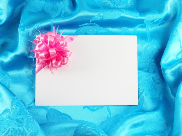 Gift card with ribbon on blue satin